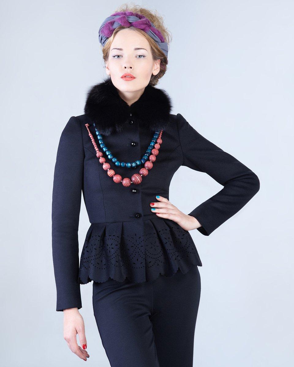 Жакет черного цвета с украшенной перфорацией баской.